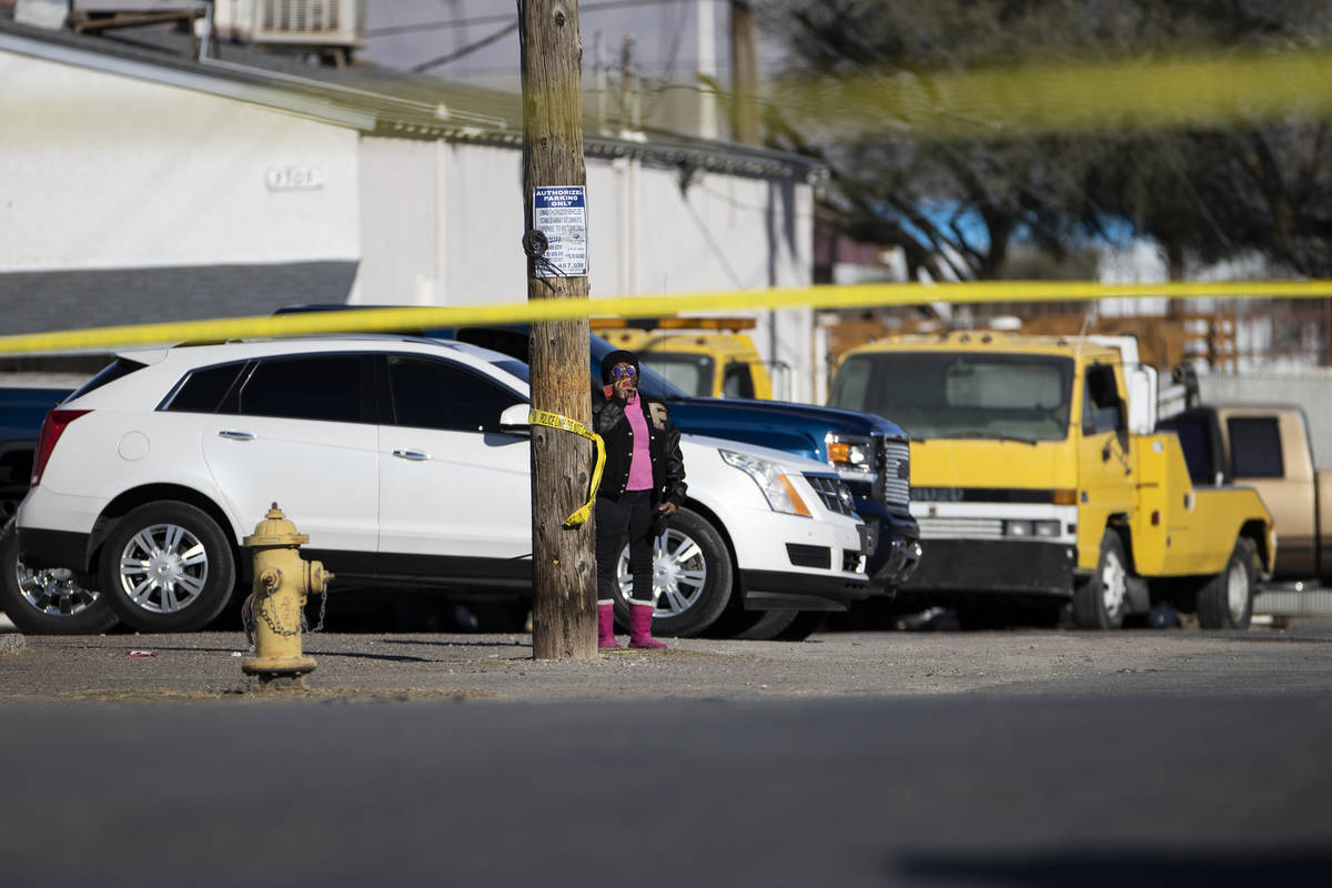 A bystander watches as police investigate the scene of a fatal shooting near the intersection o ...
