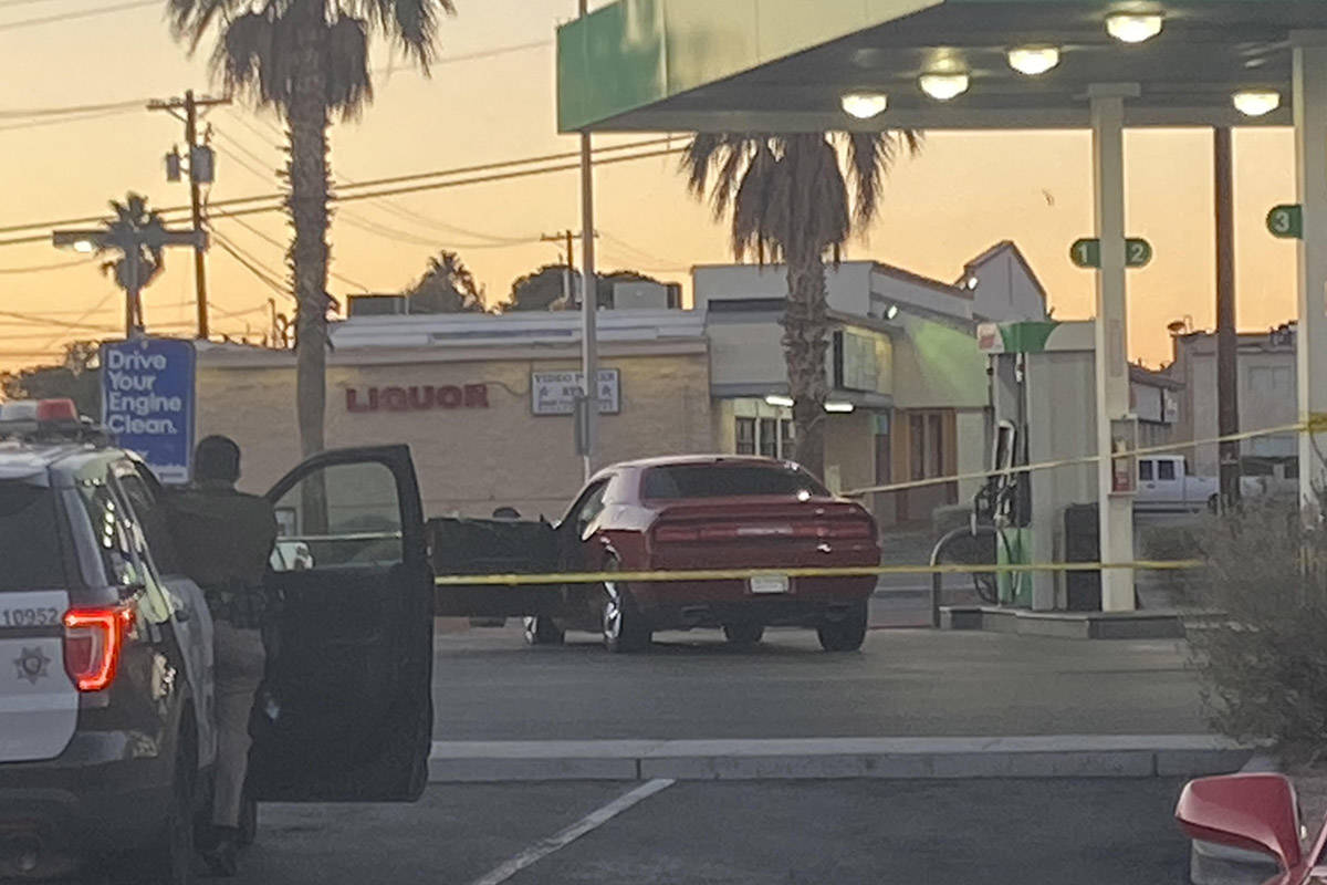 Las Vegas police surround a red Dodge car in front of a Sinclair gas station shortly after 6:30 ...
