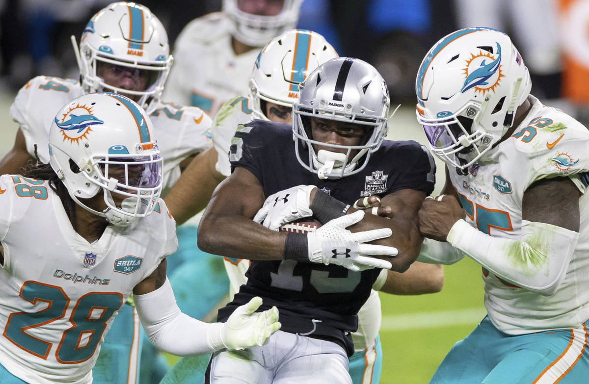 Raiders wide receiver Nelson Agholor (15) is stacked up by Miami Dolphins strong safety Bobby M ...
