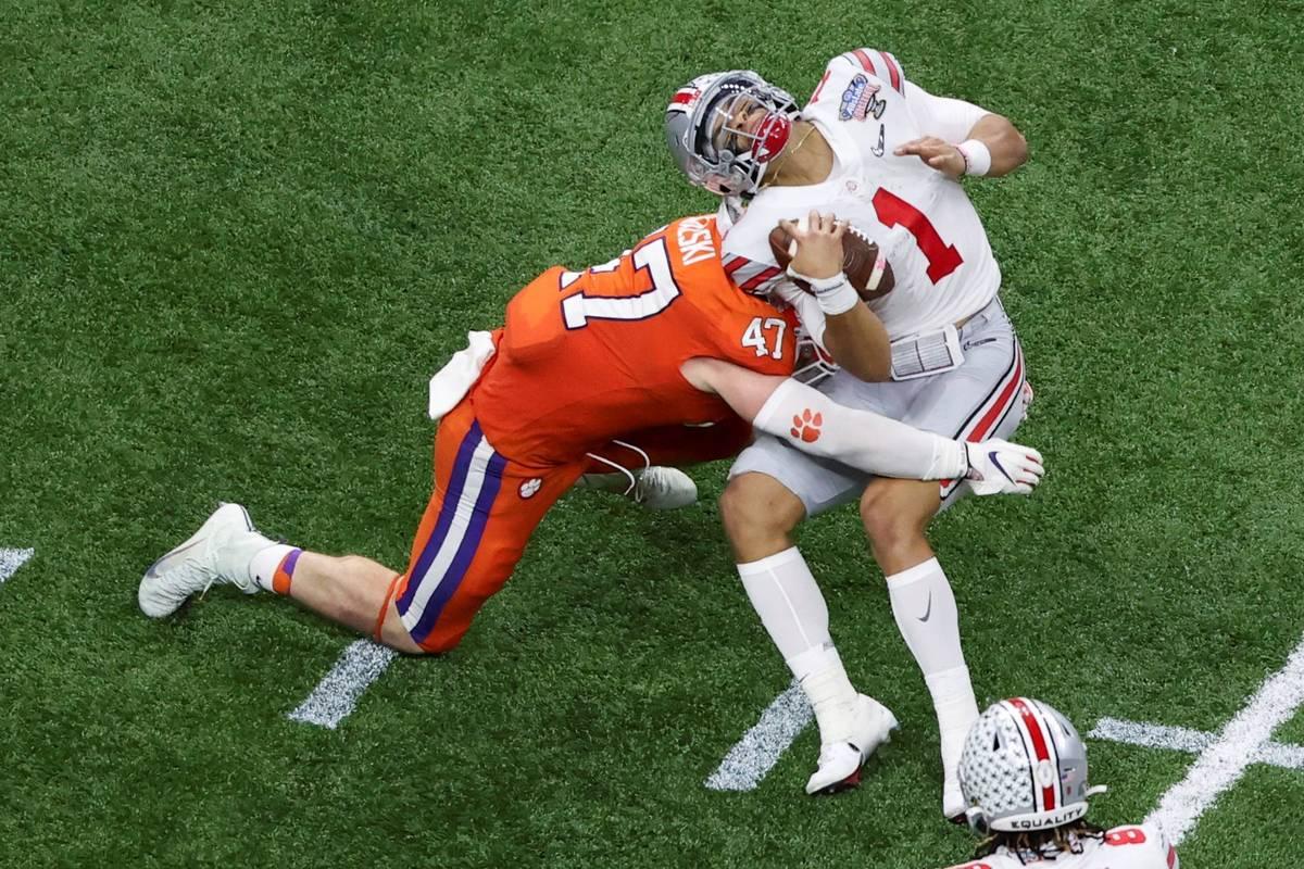 Ohio State quarterback Justin Fields gets hit by Clemson linebacker James Skalski during the fi ...