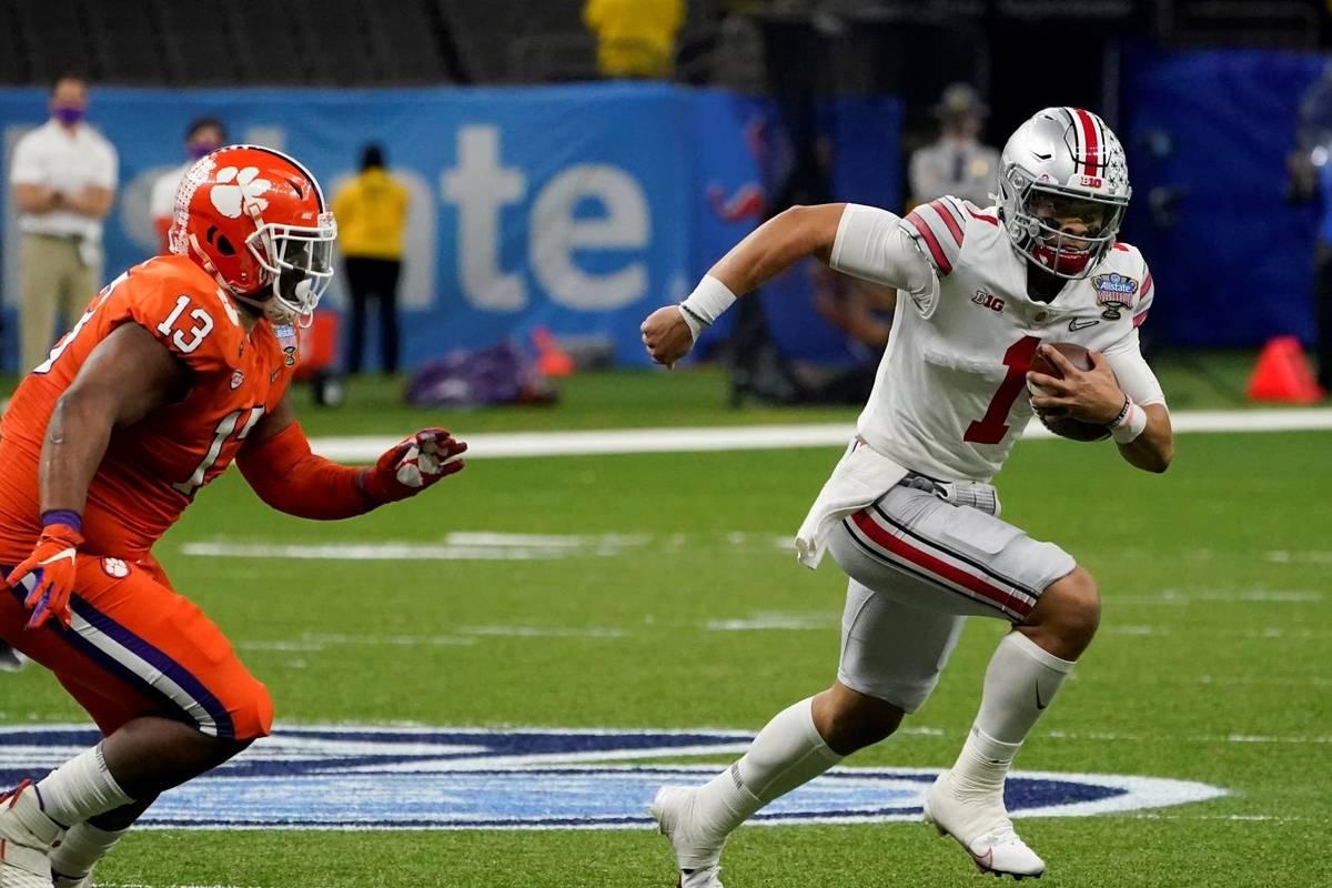 Ohio State quarterback Justin Fields runs past Clemson defensive tackle Tyler Davis during the ...