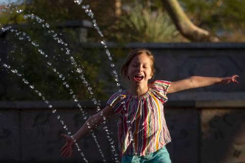 Alena Kaminski, 8, runs through the water play area at Exploration Peak Park on Saturday, Jan. ...