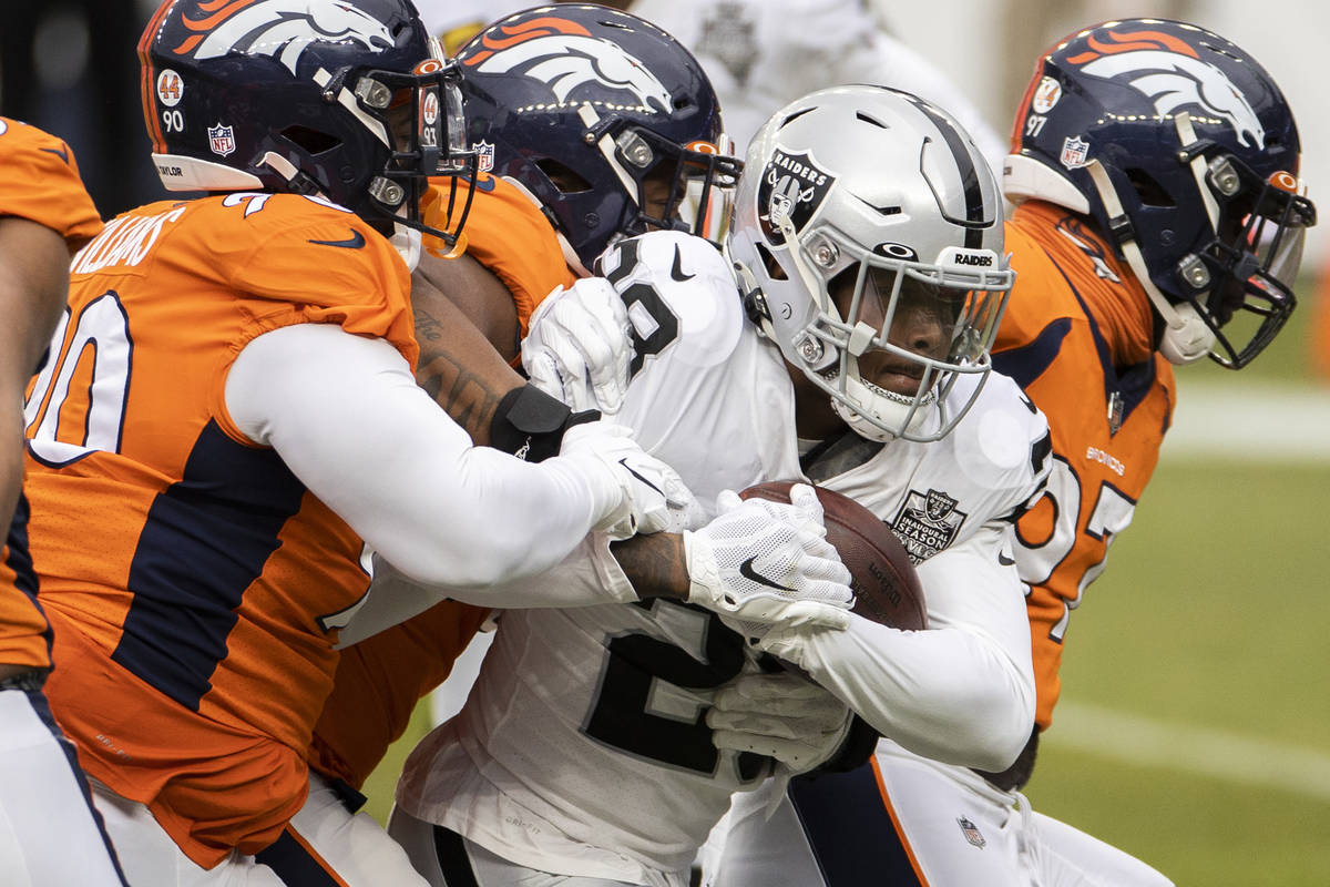 Raiders running back Josh Jacobs (28) drives forward with a group of Denver Broncos on his back ...