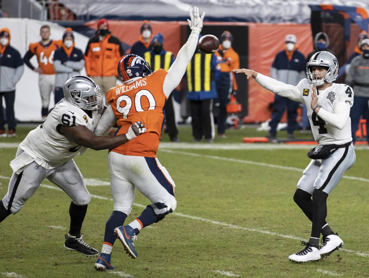 Raiders quarterback Derek Carr (4) makes a pass over Denver Broncos nose tackle DeShawn William ...