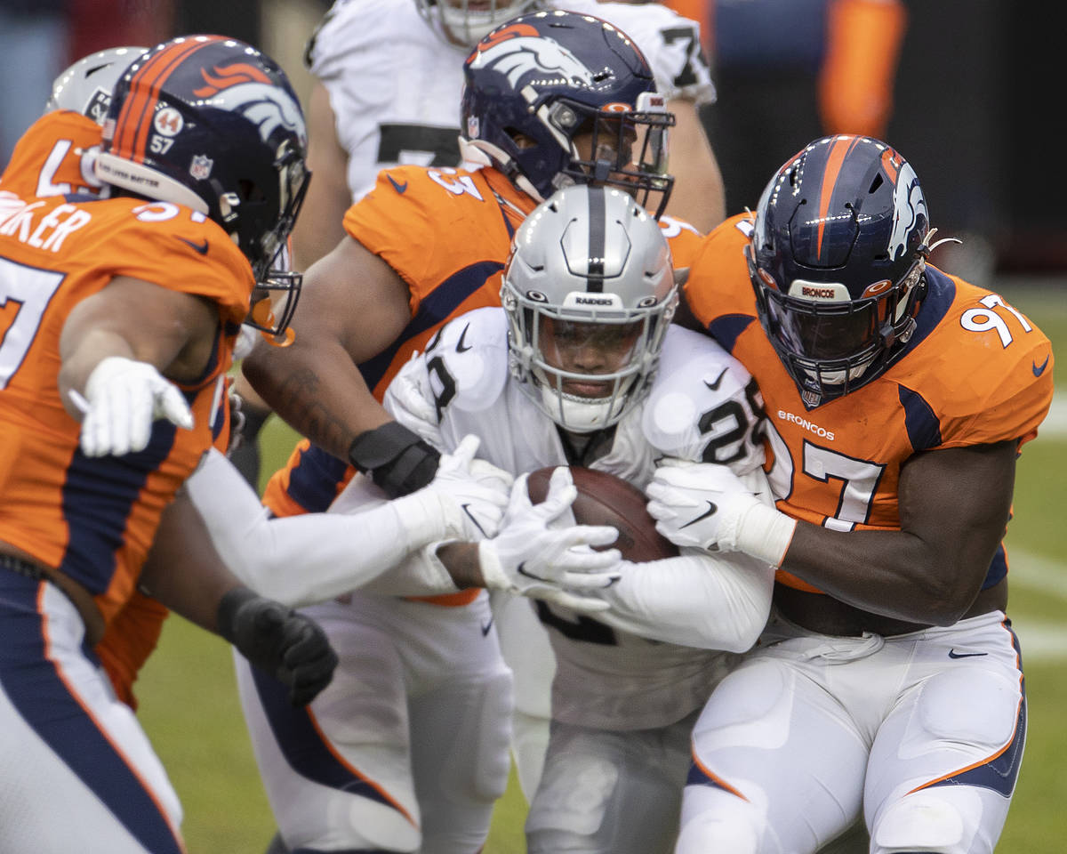 Raiders running back Josh Jacobs (28) is gang tackled by Denver Bronco defenders in the first q ...