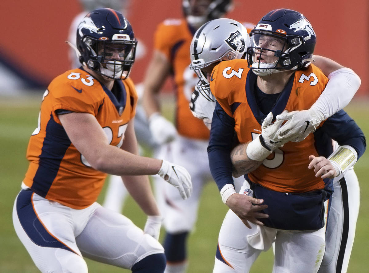Denver Broncos quarterback Drew Lock (3) is hit by Raiders defensive end Maxx Crosby (98) in th ...