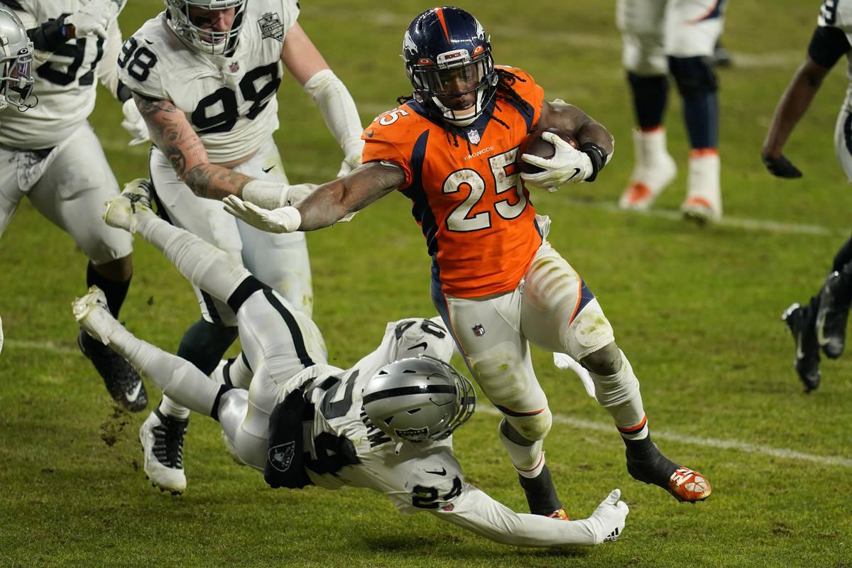 Denver Broncos running back Melvin Gordon (25) avoids a tackle by Las Vegas Raiders strong safe ...