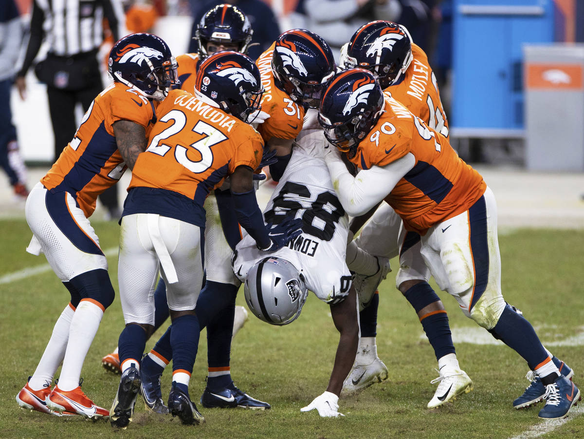 Raiders wide receiver Bryan Edwards (89) is gang tackled by Denver Broncos defenders in the fou ...