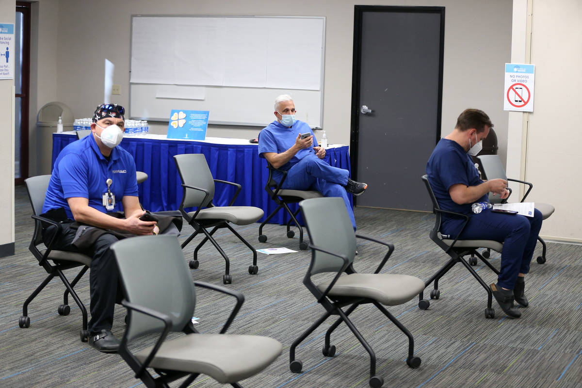 Registered Nurse Cass Petrykowski, center, waits after receiving the second dose of the Pfizer ...