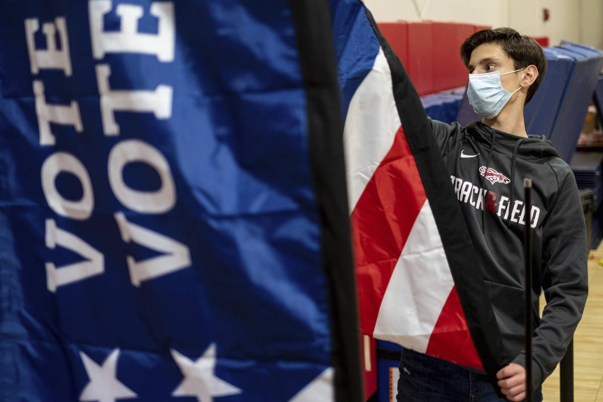 Thomas Hedrich sets up voting flags at a polling location in Gwinnett County, Ga., outside of A ...