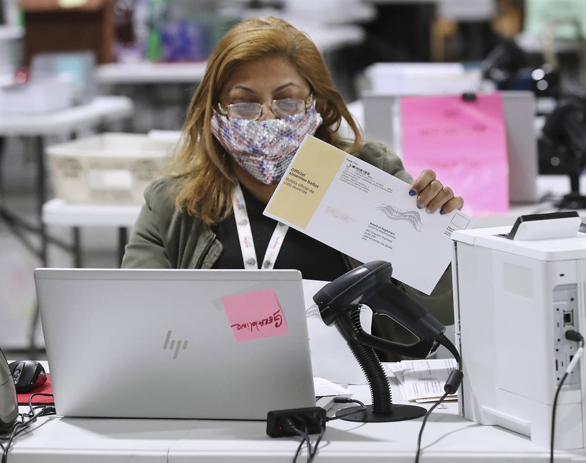 Election workers check-in, sort, and signature verify absentee ballots for the state's U.S. Sen ...