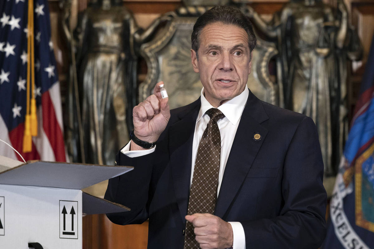 In this Dec. 3, 2020, photo provided by the Office of Gov. Andrew Cuomo, Cuomo holds up samples ...