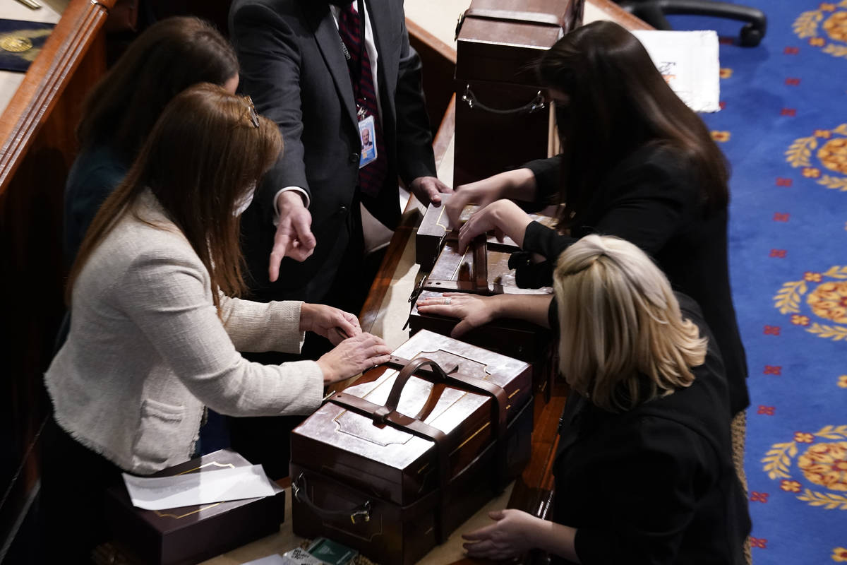 Staff members close boxes containing Electoral College votes after an objection to confirming v ...