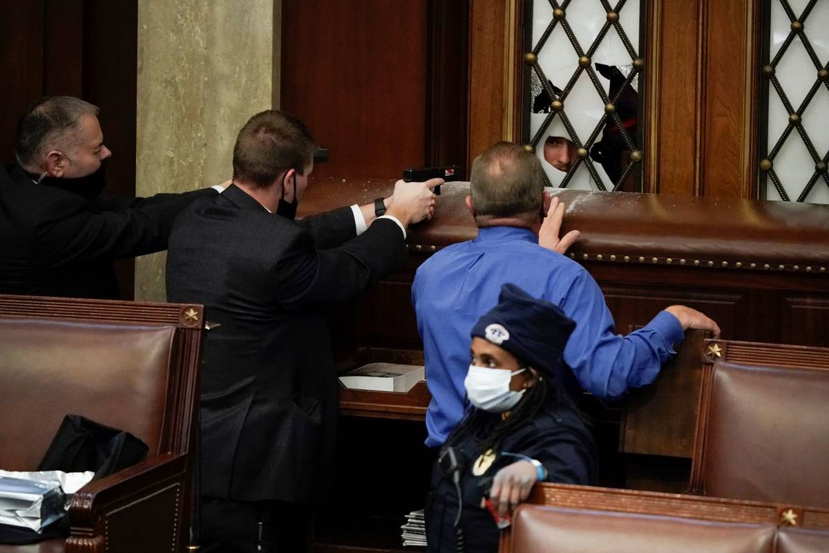 Police with guns drawn watch as protesters try to break into the House Chamber at the U.S. Capi ...