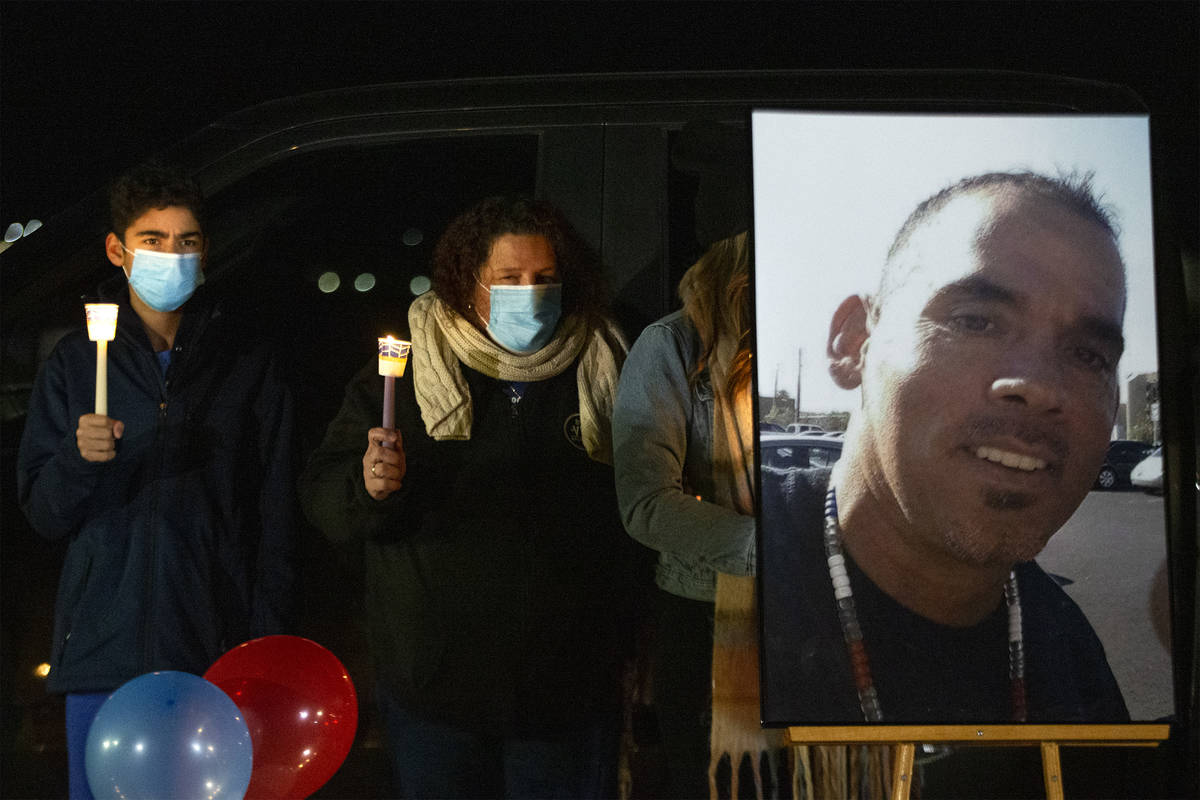 Eric Echevarria Jr., left, and his mother Annmarie Echevarria hold candles next to a photo of t ...