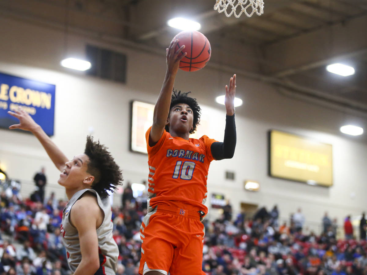 Bishop Gorman's Zaon Collins (10) goes to the basket in front of Findlay Prep's Blaise Beaucham ...