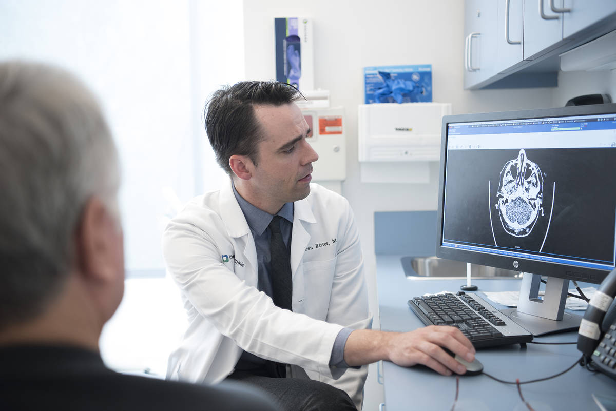 Dr. Aaron Ritter looks at a brain scan of a PABHS participant before the COVID-19 pandemic. (Cl ...