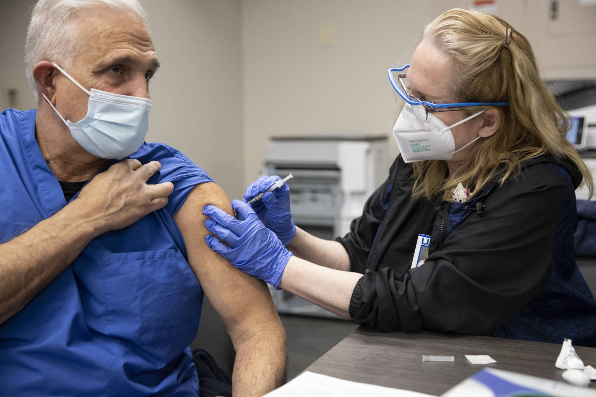 Registered Nurse Cass Petrykowski, left, receives the second dose of the Pfizer COVID-19 vaccin ...