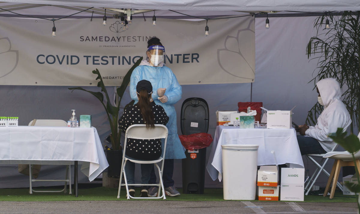 A mid-turbinate nasal swab PCR test is administered at a same-day coronavirus testing site in L ...