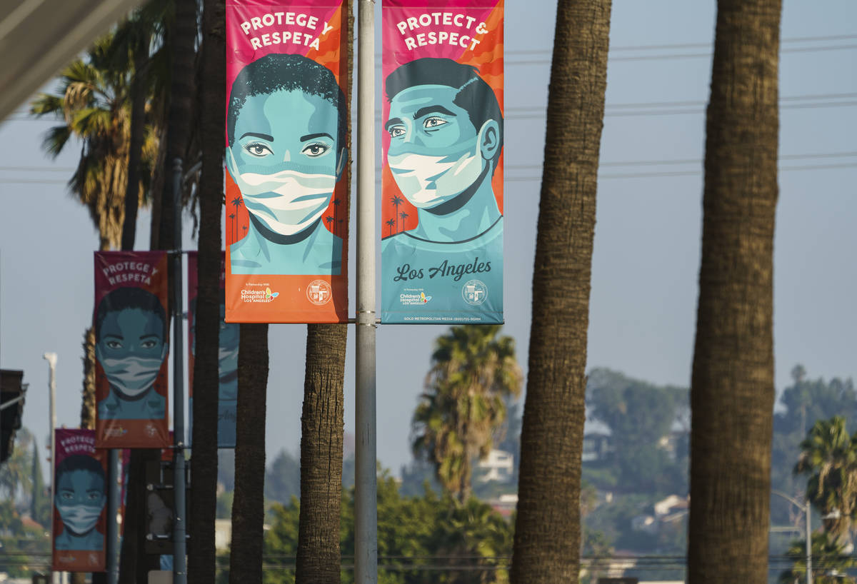Banners advising people to wear masks against the coronavirus hang along Hollywood Boulevard in ...