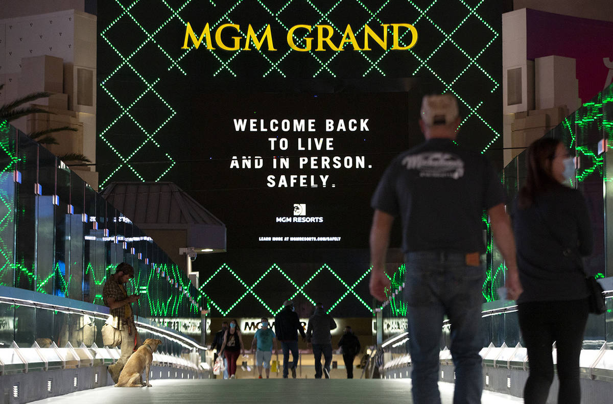 An MGM Grand marquee references coronavirus as visitors cross a pedestrian bridge on Monday, No ...