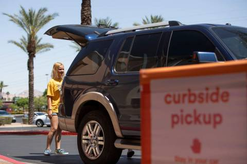 Kayla Walsh opens the trunk for an Ulta employee to put the curbside pickup order she and her m ...