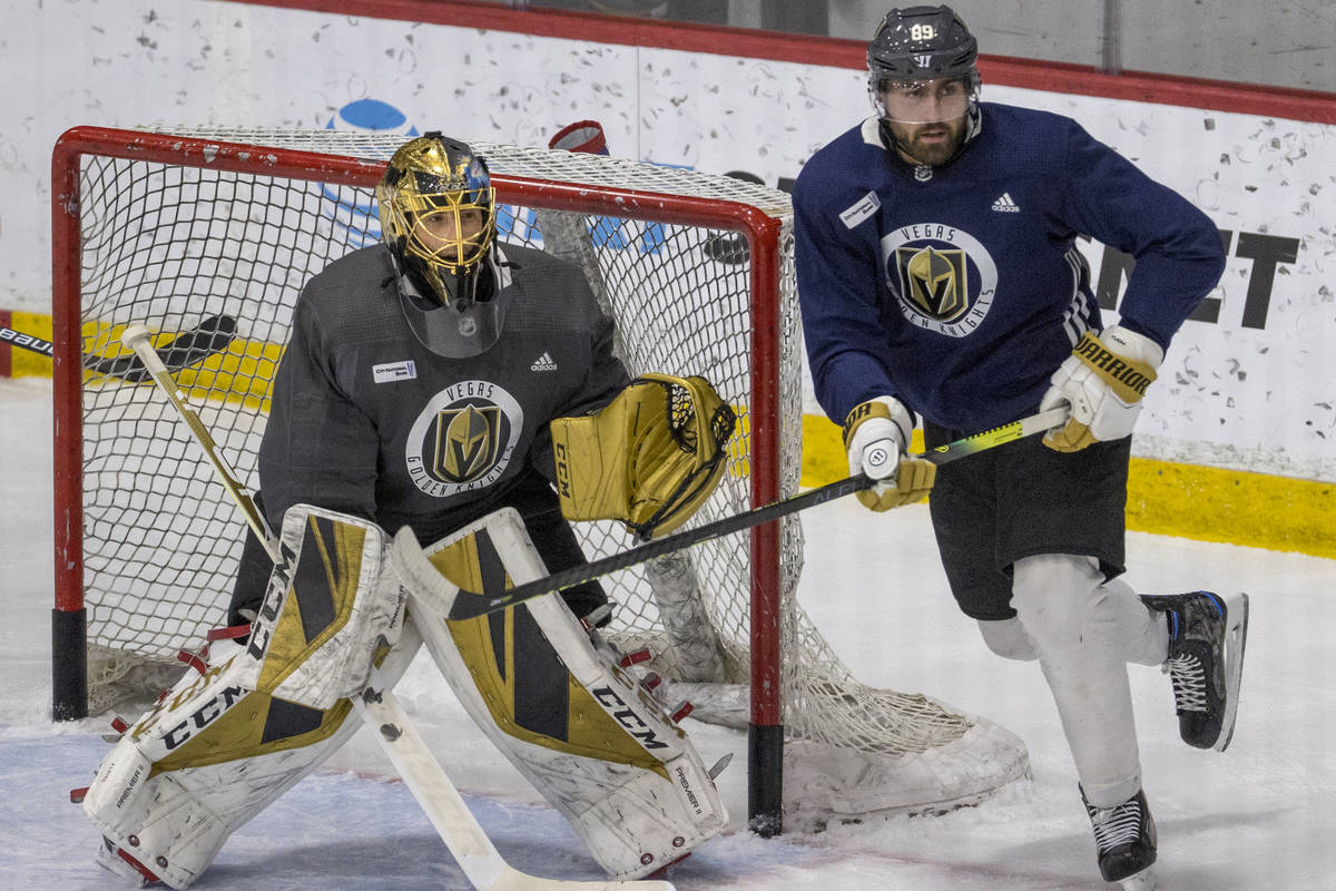 Vegas Golden Knights goaltender Marc-Andre Fleury (29, left) defends the net as right wing Alex ...