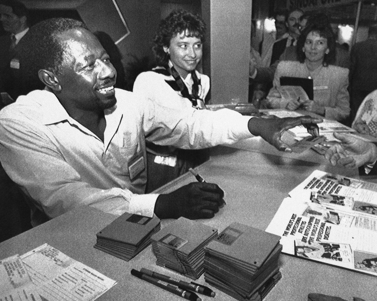 Former baseball great Henry Aaron signs autographs on computer disks at the Comdex convention i ...