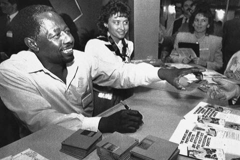 Former baseball great Henry Aaron signs autographs on computer disks at the Comdex computer sho ...