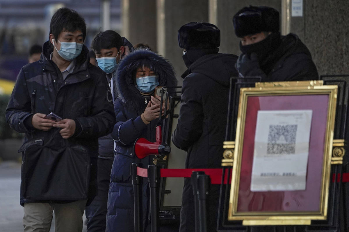 People wearing face masks to help curb the spread of the coronavirus use smartphones to scan th ...