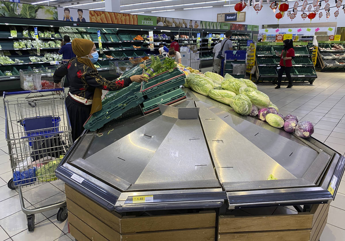 A woman shops for vegetables at a shopping mall in Kuala Lumpur, Malaysia, Tuesday, Jan. 12, 20 ...