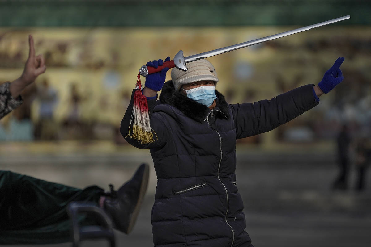 A woman wearing a face mask to help curb the spread of the coronavirus performs a morning exerc ...
