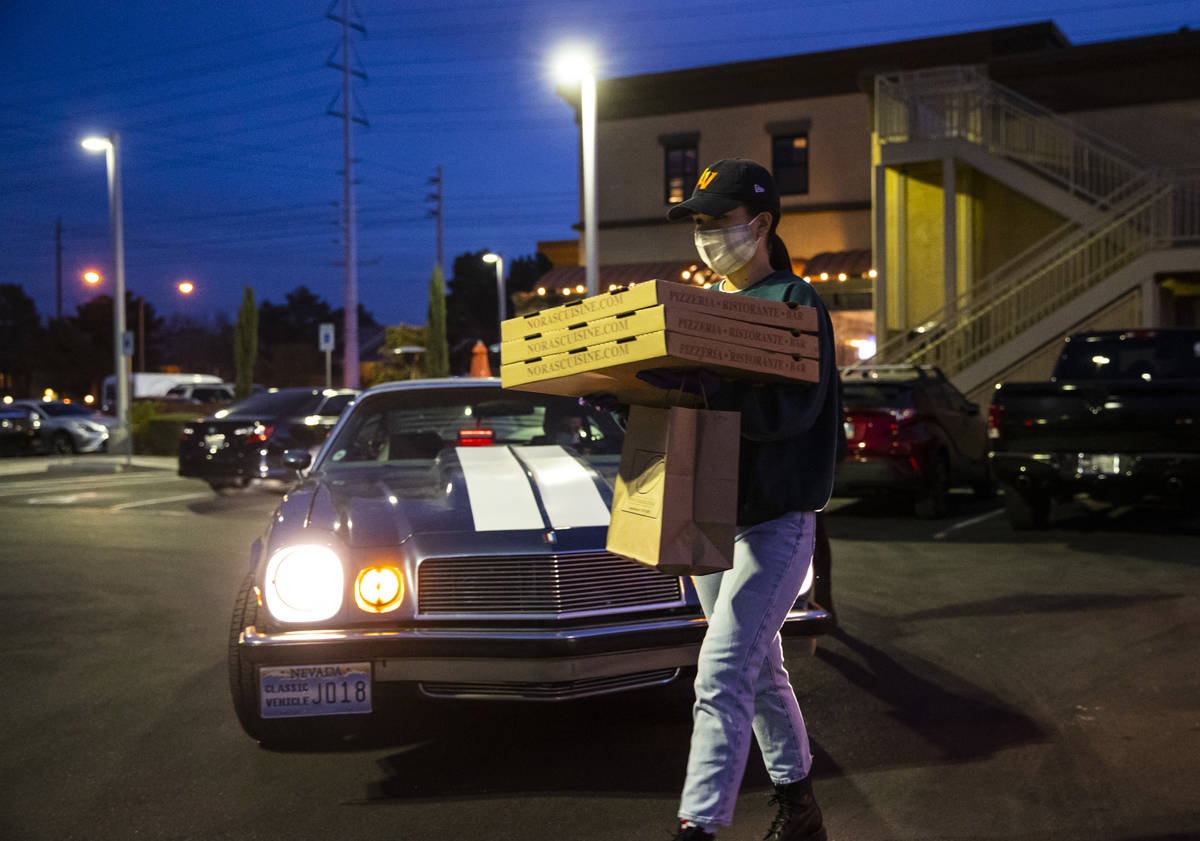 Hostess Emily Mejorada brings out food for curbside pickup at Nora's Italian Cuisine in Las Veg ...