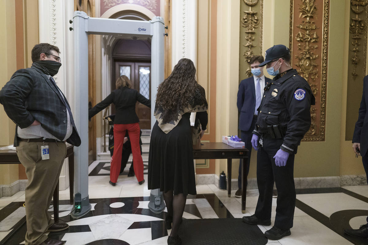 Congressional staff passes through a metal detector and security screening as they enter the Ho ...