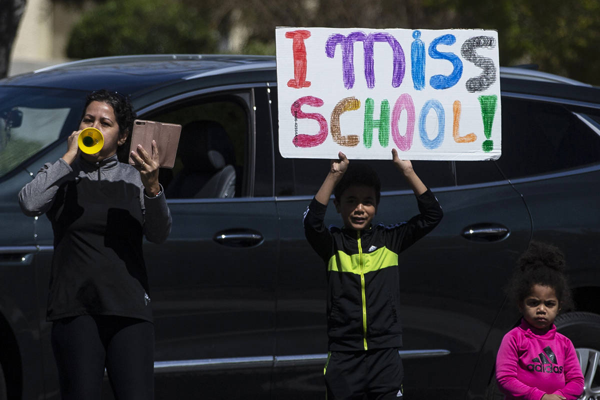 Las Vegas residents wave to teachers and staff from O'Roarke Elementary School who organ ...