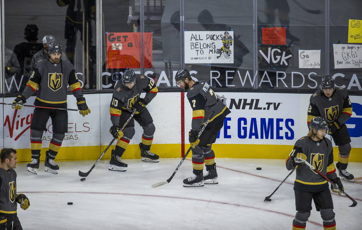Golden Knights players warm up about handwritten signs from fans during the warm ups of an NHL ...