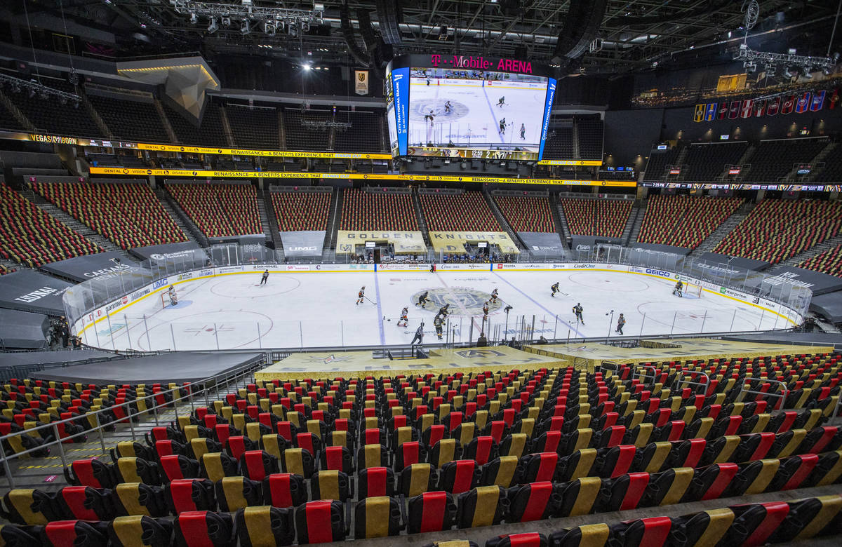 Golden Knights and Anaheim Ducks players battle to an empty arena during the first period of an ...