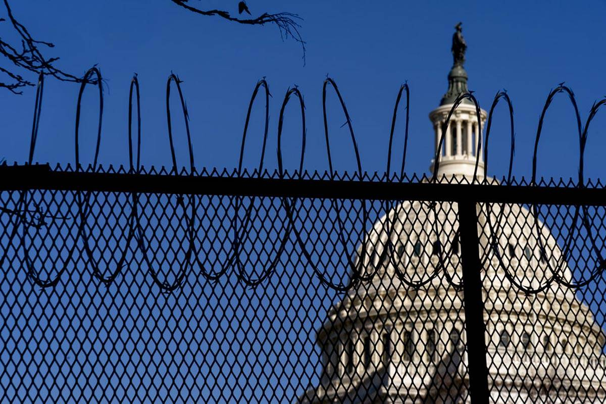 The Dome of the Capitol Building is visible through razor wire installed on top of fencing on C ...
