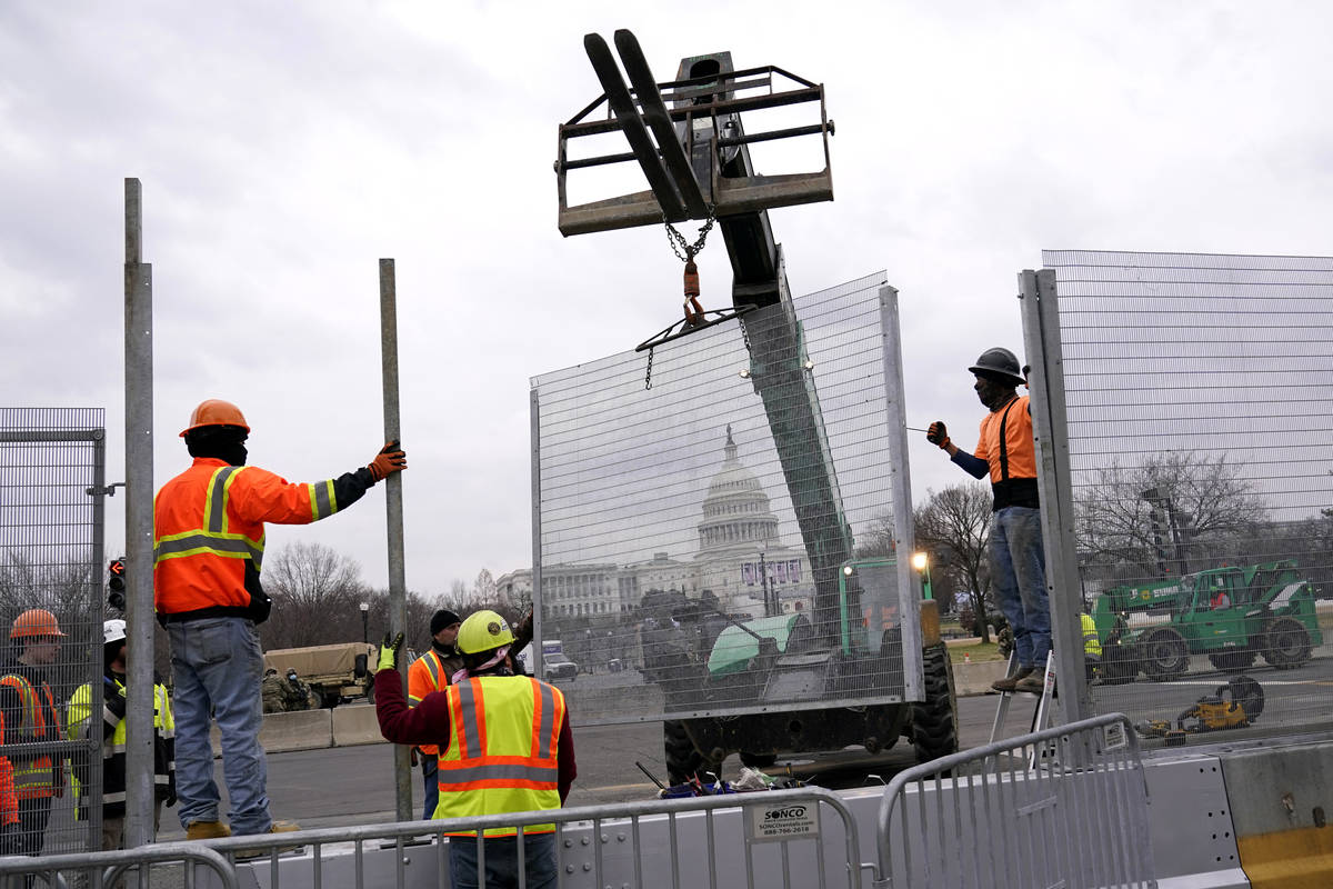 Workers install security fencing near the U.S. Capitol in Washington, Friday, Jan. 15, 2021, ah ...