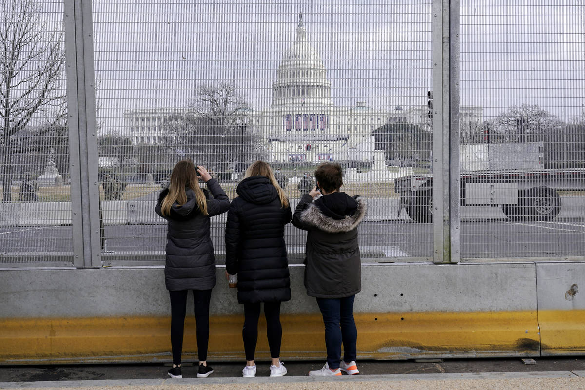 People take photos through the extensive security surrounding the U.S. Capitol in Washington, F ...
