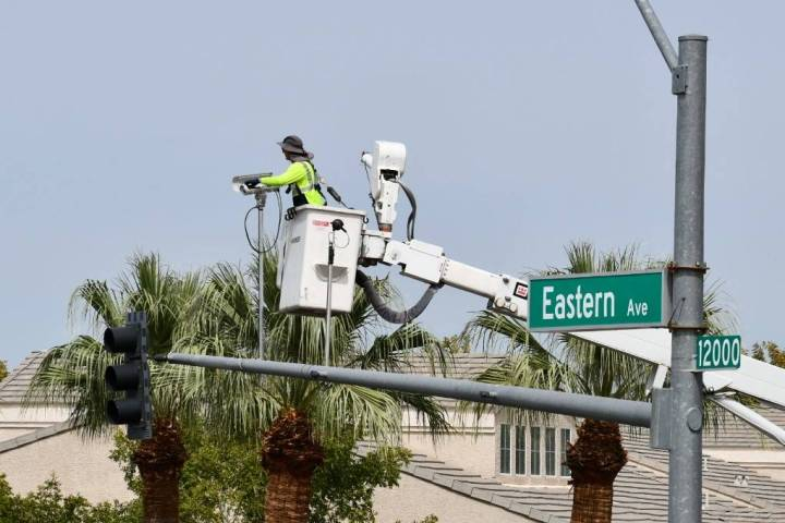 A city of Henderson worker installs adaptive traffic signal equipment as part of the a pilot pr ...