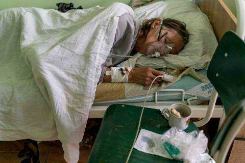A patient with coronavirus breathes wearing an oxygen mask in an intensive care unit at the hos ...