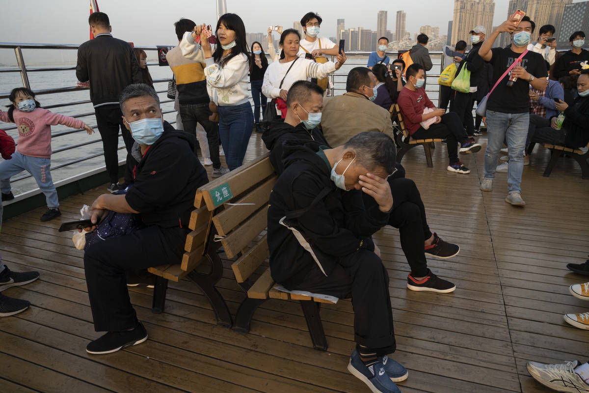 Residents, some wearing masks, ride on a ferry in Wuhan on Thursday, Oct. 22, 2020. The global ...