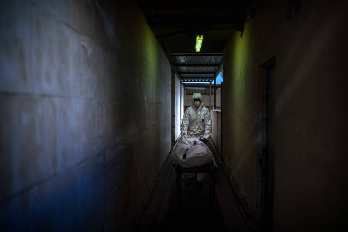 A mortuary worker transports the body of a COVID-19 victim on a stretcher at the morgue of a ho ...