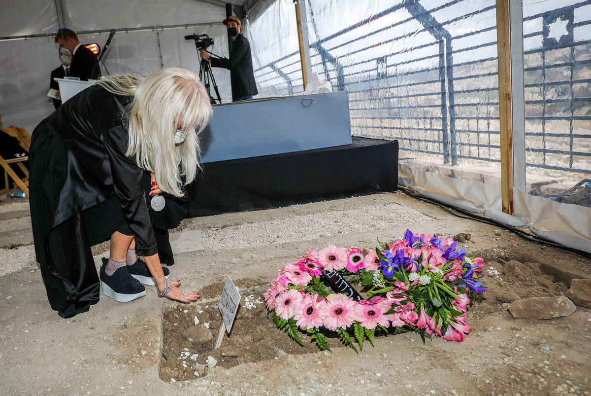 Dr. Miriam Adelson mourns next to the grave of her late husband, Sheldon Adelson, at his funera ...