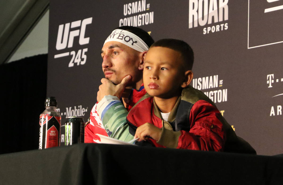 UFC featherweight Max Holloway and his son, Rush, listen to a question being asked during the U ...