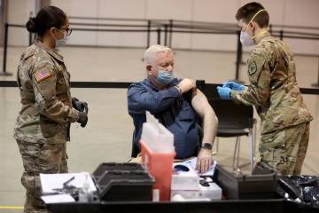 Dennis West, of Nevada Task Force One Urban Search and Rescue, receives a COVID-19 vaccination ...