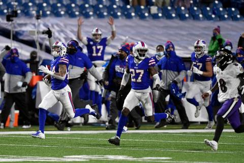 Buffalo Bills cornerback Taron Johnson, left, runs away from Baltimore Ravens quarterback Lamar ...