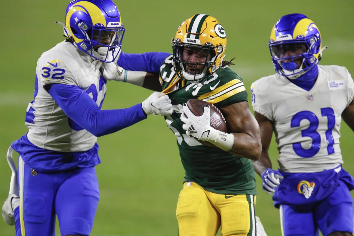 Green Bay Packers' Aaron Jones (33) is chased down by Los Angeles Rams' Jordan Fuller (32) and ...