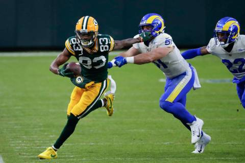 Green Bay Packers' Marquez Valdes-Scantling (83) pushes off Los Angeles Rams' Troy Reeder (51) ...